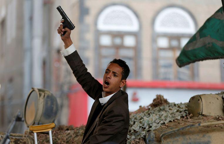 Een Houthi-rebel reageert vanaf een tank in Sanaa op de dood van ex-president Saleh. Beeld REUTERS