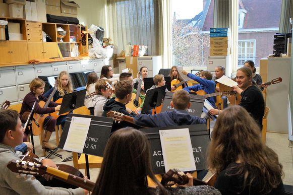 De leerlingen in de gitaarklas van de Academie voor Muziek en Woord zitten op elkaar gepakt.