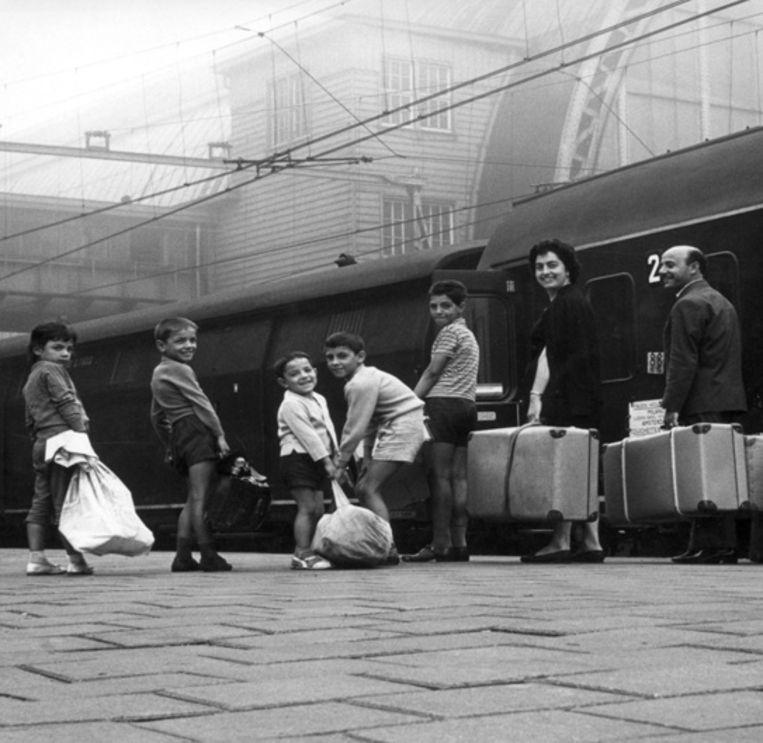 1961, een Italiaanse gastarbeider haalt zijn gezin op van Amsterdam CS. © Nationaal Archief Beeld