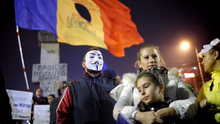 Demonstranten vrijdag in Boekarest. Net als bij de protesten tegen Ceausescu in 1989 worden vlaggen met een gat erin gedragen om de afkeer van de politieke klasse te benadrukken. Beeld EPA