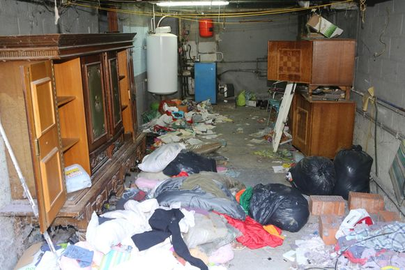 In de garage staan kasten en ligt de grond vol kleren en linnen.