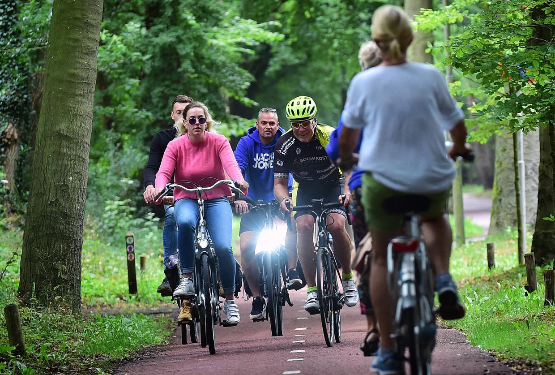 Drukte op de fietspad bij de Eeuwigelaan in Bergen. Inwoners willen dat er een tweede fietspad bijkomt, ten koste van het wandelpad. De bewoners van de straat liggen dwars.  Beeld Marcel van den Bergh / de Volkskrant