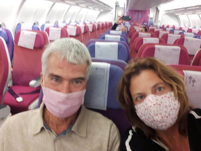 Ien van den Heuvel en Nick van den Bossche op een vlucht van Laos naar Thailand in een bijna leeg vliegtuig, terwijl tal van wanhopige reizigers ook mee hadden gewild.