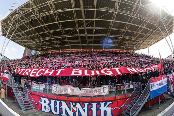 Een stadion vol supporters staat stil.