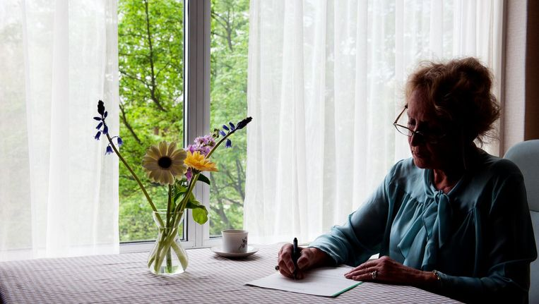 Een oude dame in een aanleunwoning tekent de wilsverklaring. Beeld anp