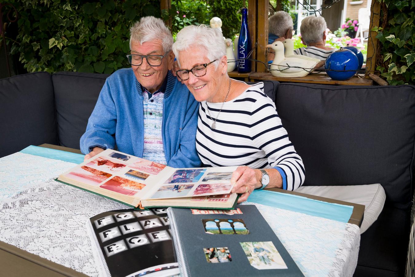 Jan bladert met zijn vrouw Ria door één van de fotoalbums met vakantiekiekjes en haalt herinneringen op.
