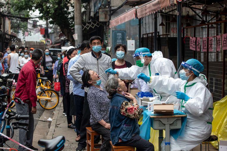 Inwoners van de Chinese stad Wuhan worden gecontroleerd op het coronavirus. Beeld AFP