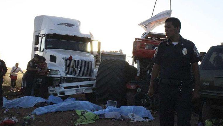 Een agent staat bij de bedekte slachtoffers van het ongeval met de monstertruck. Beeld reuters