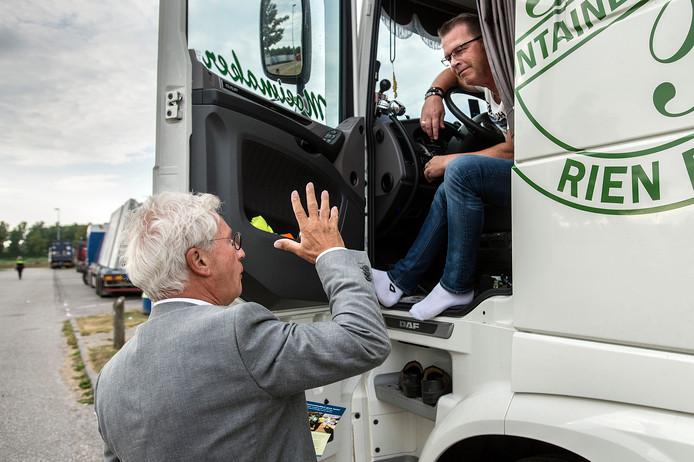 Burgemeester Jac Klijs van Moerdijk deelt  flyers uit aan vrachtwagenchauffeurs op parkeerplaats Streepland om hen te wijzen op het gevaar dat verstekelingen uit vooral Albanië stiekem met hen meereizen.