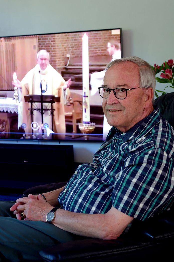Peter de Rooij in zijn woonkamer in Roosendaal, met op de achtergrond een fragment uit een mis waarin hij zelf voorgaat en die via Kerk-TV te zien is, live om 9.30 uur of later op een ander tijdstip dat beter uitkomt.