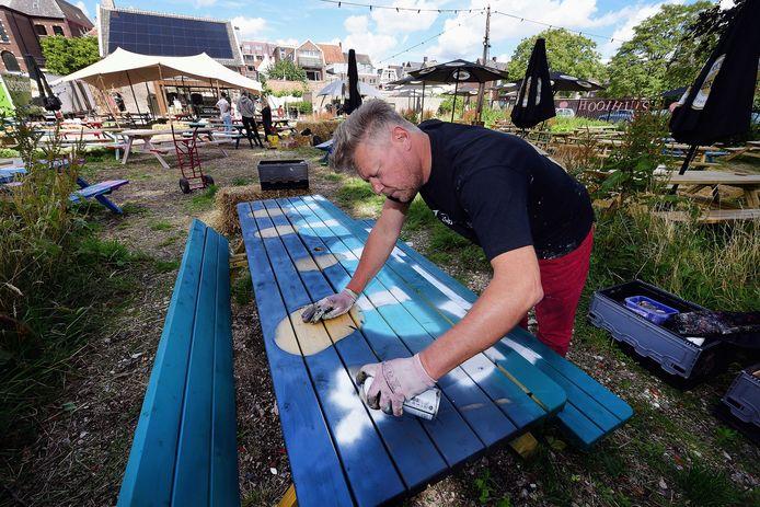 De Roosendaalse kunstenaar Geoffrey Wijn beschildert een picknicktafel.