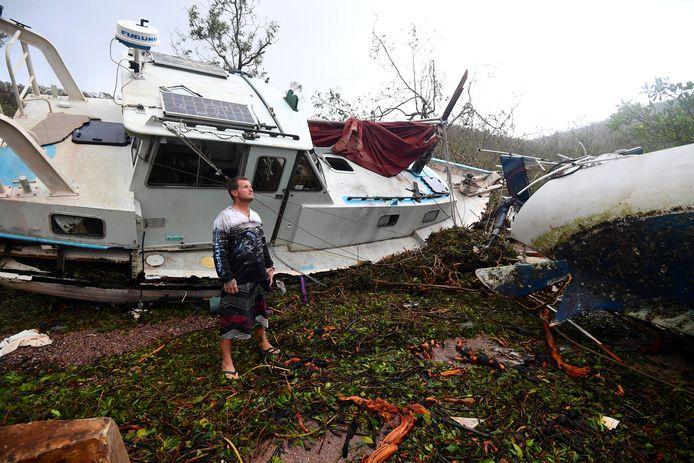 Bradley Mitchell staat voor enkele beschadigde boten in de Australische havenstad Townsville.