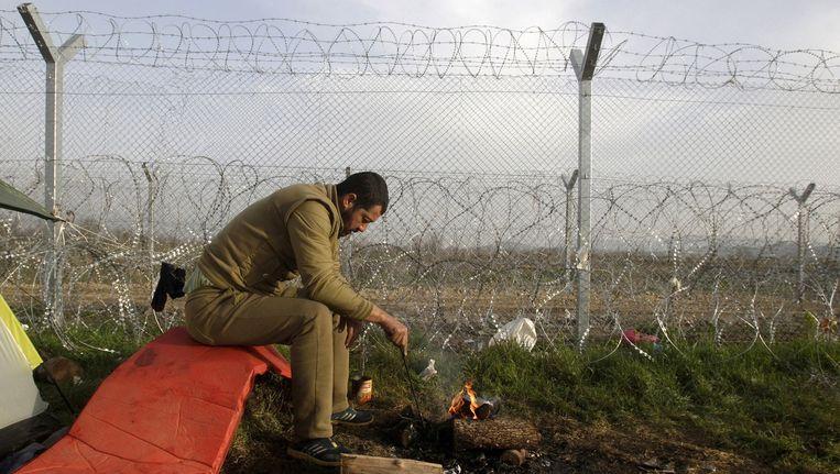 Een migrant kampeert bij de grens van Macedonië. Beeld reuters