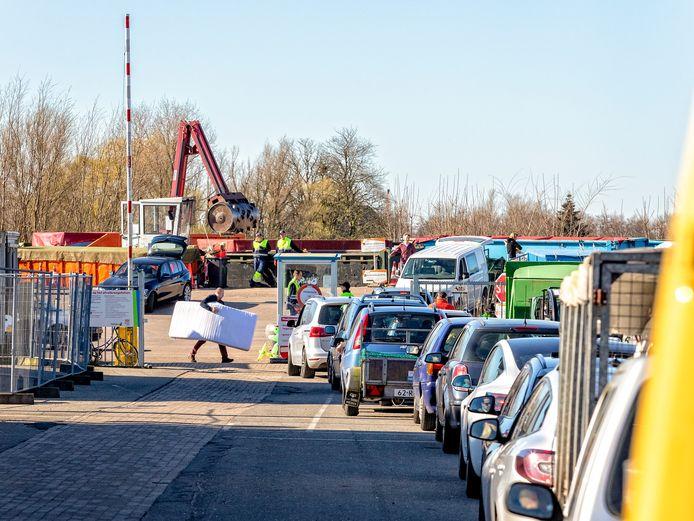 """File voor het afvalbrengstation in Gouda. Vanwege het coronavirus mogen maar vijf auto's tegelijk op het terrein aanwezig zijn. Medewerker van het afvalbrengstation Nick Langeraar vindt het opvallend druk. ,,Zo'n file zien we hooguit een keertje in de zomer""""."""