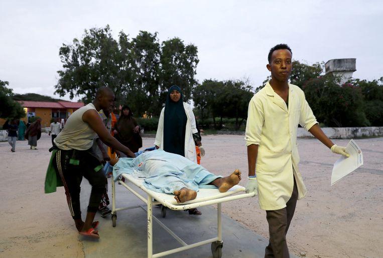 Nooddiensten bij het Madina ziekenhuis na de ontploffing in het Elite Hotel bij Lido Beach in Mogadishu. Beeld REUTERS