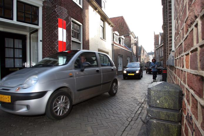 In de smalle Brouwerstraat in Blokzijl ontstaan voortdurend problemen omdat auto's elkaar nauwelijks kunnen passeren.