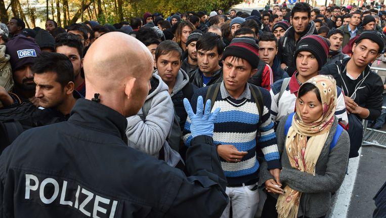 Een Duitse agent spreekt de vele vluchtelingen bij de grens met Oostenrijk toe. Beeld AFP