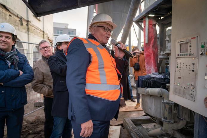 Wethouder Hans de Vroome legt uit wat hij doet met een machine om de mortelsilo voor de damwanden van de nieuwe Hoogvliet op gang te brengen. Op de achtergrond kijkt Spar-uitbater Cyriel van Gorkum (met bruine jas) toe.