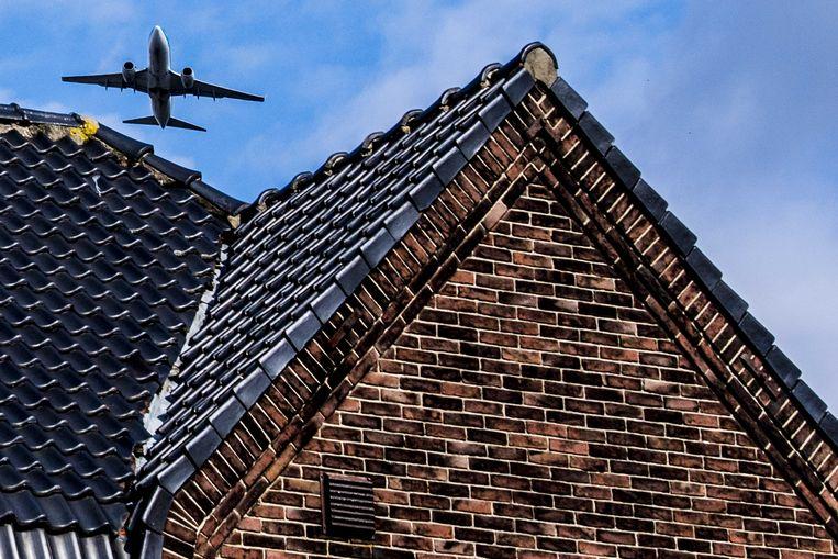 Een vliegtuig vliegt over een huis in de omgeving van Schiphol, een van de drukste luchthavens van Europa.