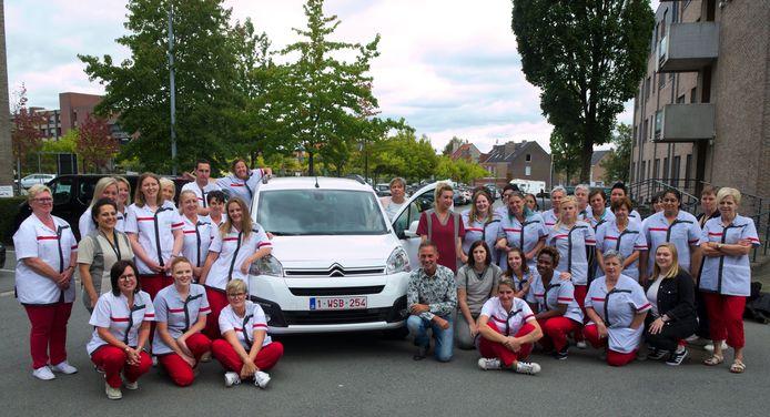 Medewerkers van de dienst Gezinszorg en schepen voor Sociale Zaken Patrick Vermeulen bij het elektrische voertuig.