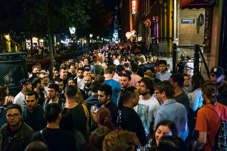 Enorme drukte op de Oudezijds Achterburgwal in Amsterdam, zaterdagavond. Voor politie en hulpverleners is er geen doorkomen aan. Beeld Marcel Wogram / de Volkskrant