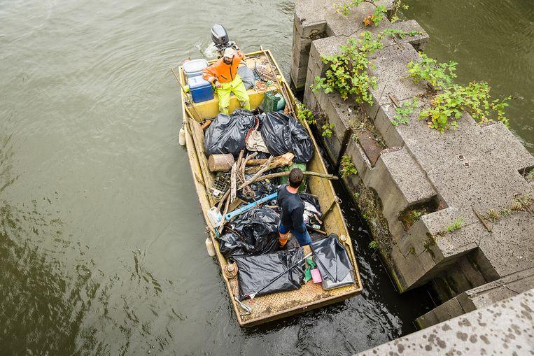 De vuilnisboot vist afval op aan de Brabantdam.