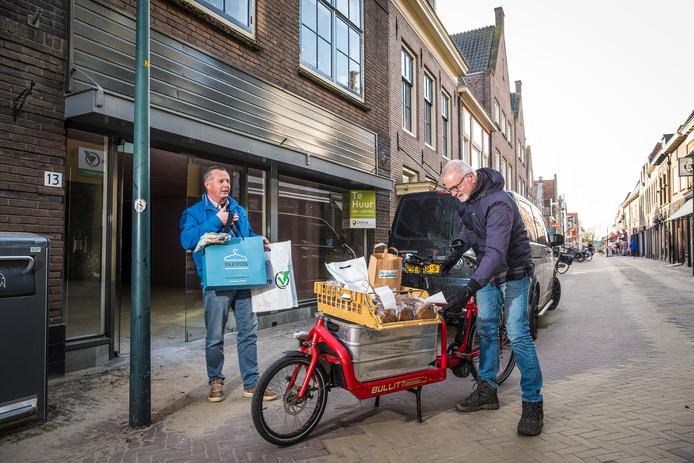 Richard Meulman van de Leckernij (links) en vrijwillige fietskoerier Hans Havinga bij het distributiepunt van Hattem Bezorgt.