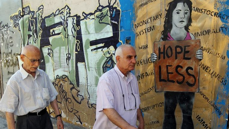 Griekse inwoner lopen langs een graffiti over de economische crisis in het land. Griekland heeft vandaag een nieuwe regering gevormd. Beeld null