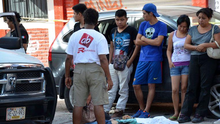 Archieffoto van enkele mensen die rond het lichaam van een doodgeschoten politieman staan in de Mexicaanse stad Chilpancingo.