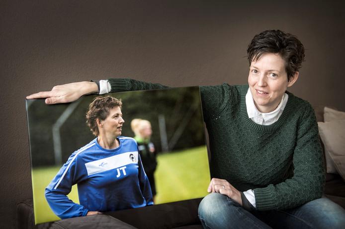 Judith Thijssen poseert met een foto van zichzelf als trainer op het veld bij Achilles'29.
