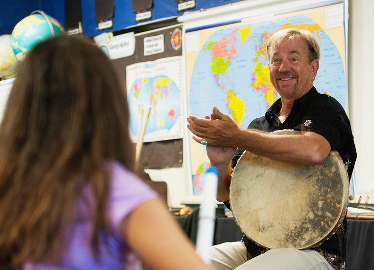 Muziekleraar John Zeretzke applaudiseert voor zijn leerlingen na een repetitie.