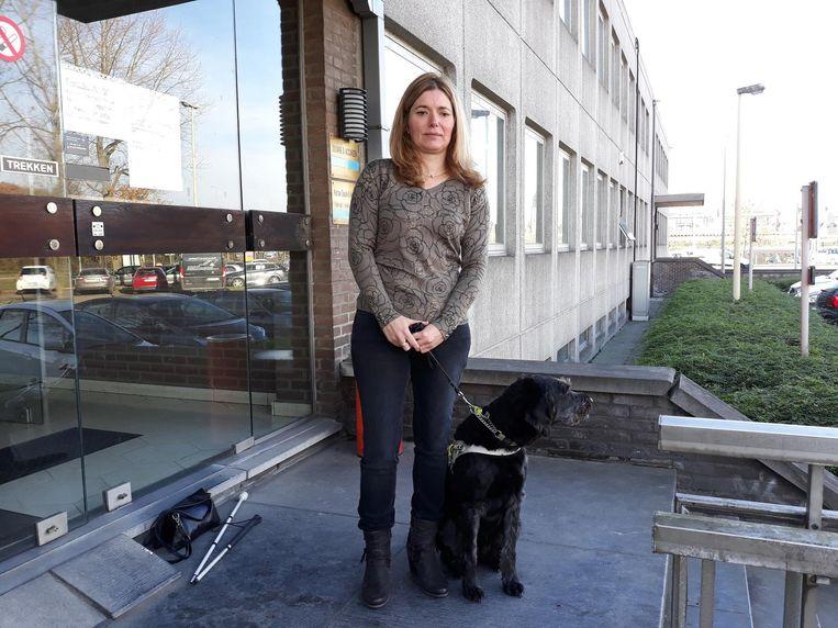 Kathleen Boogmans en haar geleidehond aan de ingang van Transkript.