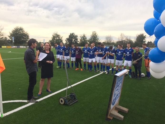 Het eerste elftal van Fc de Rakt luistert naar voorzitter Jan van den Elzen en wethouder Ingrid Verkuijlen (let op de pumps) bij de officiële opening van het nieuwe kunstgrasveld.