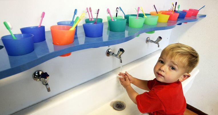 Een jongetje wast zijn handen bij de kinderopvang. Beeld anp