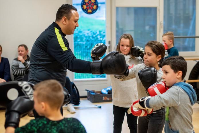 Om de beurt mogen de kinderen inslaan op de handschoenen van Jhon van Beukering.