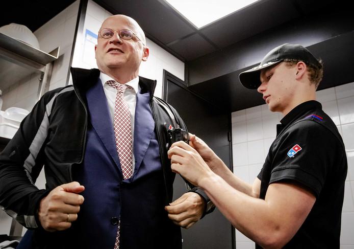 Minister Ferd Grapperhaus van Justitie krijgt een bodycam omgehangen van een medewerker van Domino's in Rotterdam. Daar daalde het aantal overvallen op maaltijdbezorgers sterk door het dragen van de camera's.