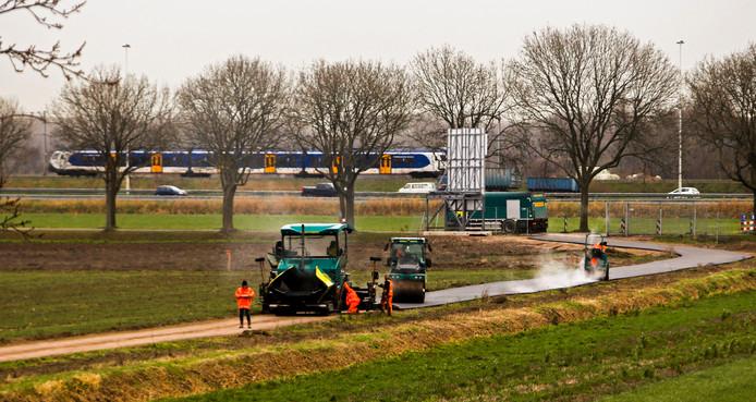 Een aannemer was gisteren bezig met het aanleggen van een asfaltweg tussen de Rijksstraatweg en de dijk.