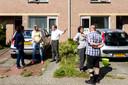 Buren komen elkaar op straat tegen om te praten over de actie van woningbouwvereniging.
