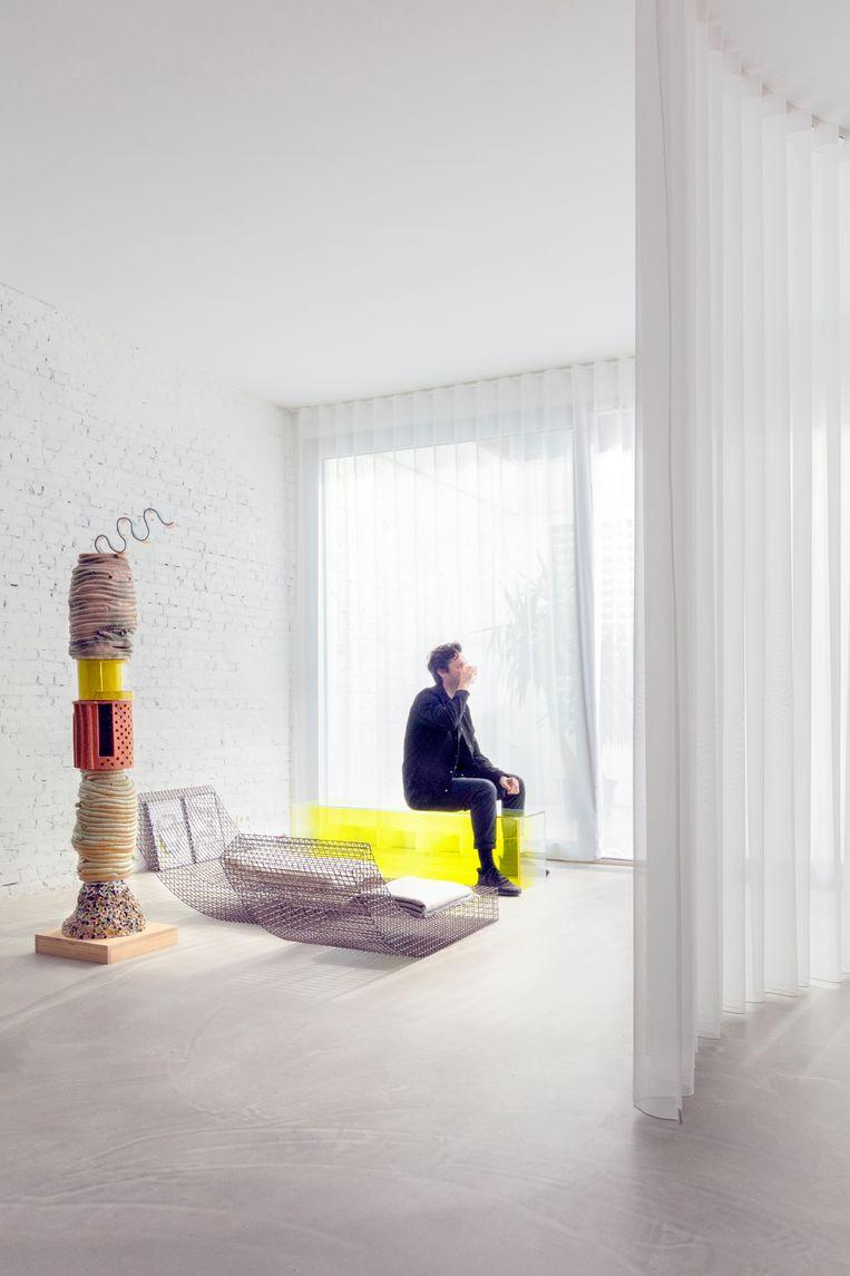 'We hebben twee totempalen in huis, deze is van keramiek, gemaakt door Koen Taselaar, een Rotterdamse kunstenaar. We vinden dit ding geniaal en worden er blij van. Koen moet nog een lamp van me krijgen, want we hebben 'm geruild, maar die ben ik nog steeds aan het ontwerpen.'  'Het zitobject is van Muller van Severen. Het heet 'Wire s' en is van staal gemaakt.'  Sabine: 'Ik heb vorig jaar een installatie gemaakt waarvoor ik een schilderij van Mondriaan 'uit elkaar heb getrokken'. Op die manier ontstond een driedimensionale ruimte. Dit gele blok is een deel van die installatie. Ons huis staat vol met prototypes en restjes van oude projecten.' Beeld Marleen Sleeuwits