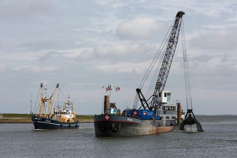 Een baggerschip is bezig de toegang tot de haven van Lauwersoog uit te baggeren. Beeld null