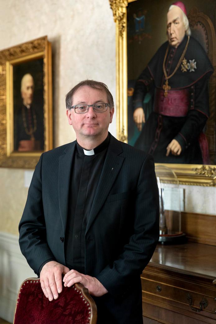 Ron van den Hout poseert in het bisschopshuis van Den Bosch bij het portret van bisschop Joannes Zwijsen, geboren in Kerkdriel, in de parochie die Van den Hout nu verlaat.