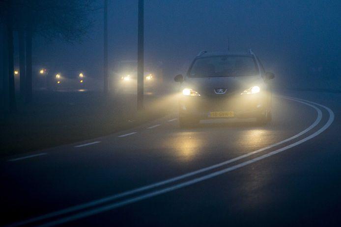 Een auto rijdt door de mist.