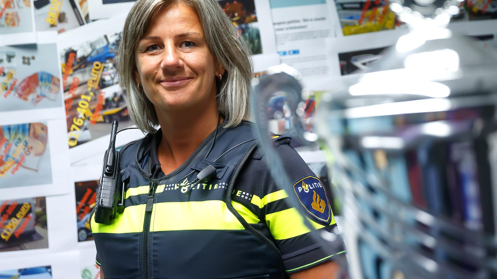 Politieteam Weerijs is politieteam van het jaar geworden omdat het zo goed geld weet af te pakken van criminelen. Op de foto teamchef Jacoline Bolle voor de 'afpakmuur' met foto's van een deel van de oogst.