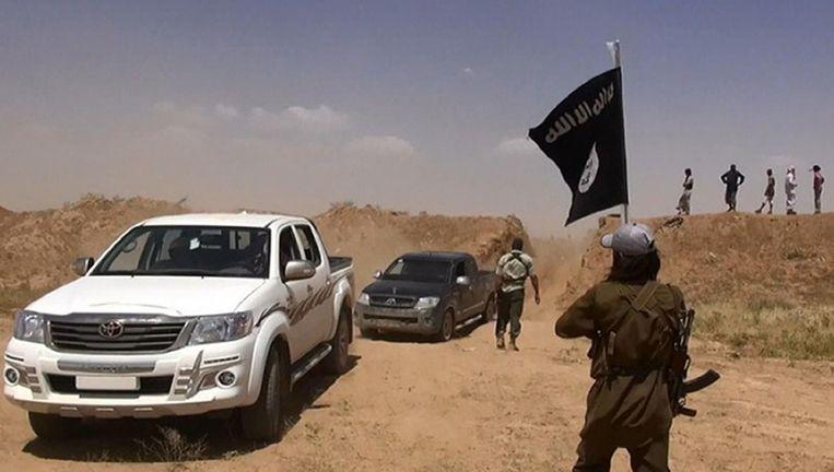 Een IS-strijder zwaait met een vlag op de grens van Irak en Syrië. Beeld AFP