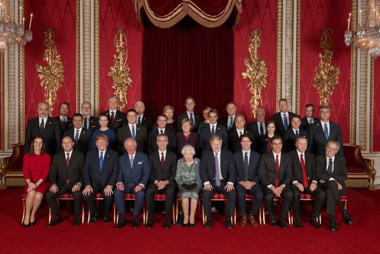 De staatshoofden en regeringsleiders van de Navo-landen samen met de Britse koningin Elisabeth en prins Charles, dinsdag in Buckingham Palace.   Beeld Reuters