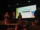 Kim Tchai is blij met de zojuist verkregen Rotterdamse Ondernemersprijs. Wethouder Barbara Kathmann (l) en presentatrice Merel Westrik (m) flankeren haar.
