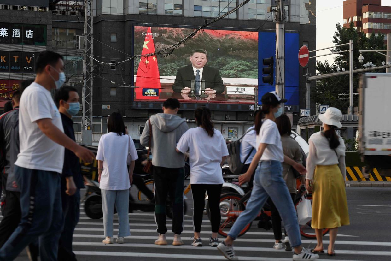 Op een groot scherm in Peking viel te zien hoe president Xi de Wereldgezondheidsorganisatie toesprak. Beeld AFP