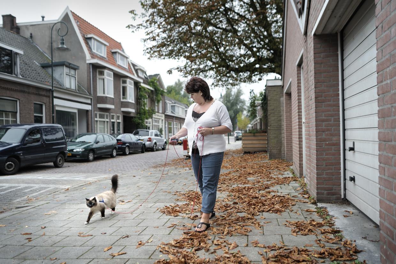 Vrouw laat haar kat Oreo (naar de koekjes) uit in een Utrechtse volkswijk. Beeld Joost van den Broek