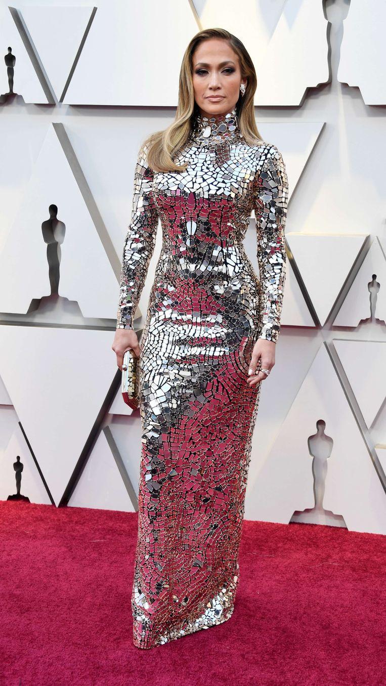 Jennifer Lopez...zou Jennifer Lopez niet zijn als ze niet zou opvallen. Ze ziet eruit als een sexy discobal aan de arm van vriendje Alex Rodriguez. De 49-jarige zangeres werkt hard aan haar lichaam en het mag dan ook gezien worden. De zilveren jurk is overigens van Tom Ford.