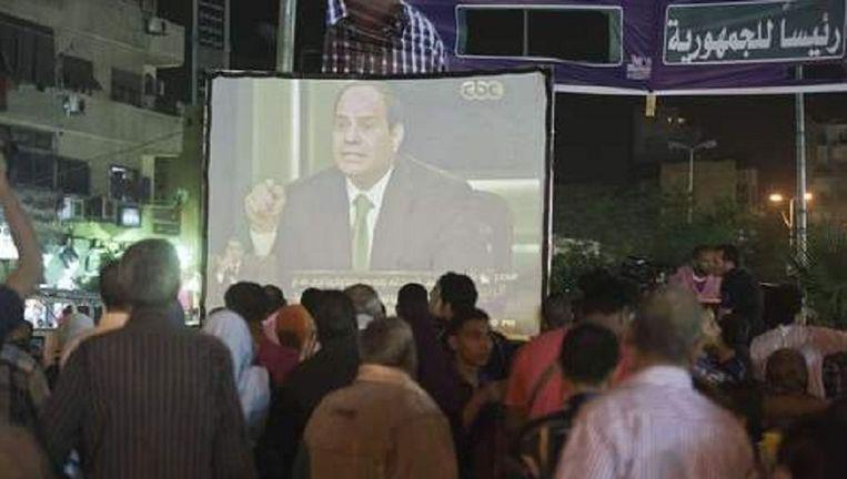 Op straat in Caïro wordt het interview met Sisi op een groot scherm uitgezonden